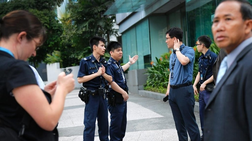 Singapore policemen stop pedestrians and attendees of the 14th International Institute for Strategic Studies Shangri-la Dialogue, or IISS, Asia Security Summit, from entering the vicinity, Sunday, May 31, 2015, in Singapore. Police stepped up security around the venue of the international security conference Sunday following a shootout at a roadblock in which officers fatally shot one man and detained two others. The security conference, a major event in the Asia-Pacific region attended by U.S. Secretary of Defense Ash Carter and delegates from dozens of countries from around the world, was uninterrupted but access to the venue was restricted. (AP Photo/Wong Maye-E)