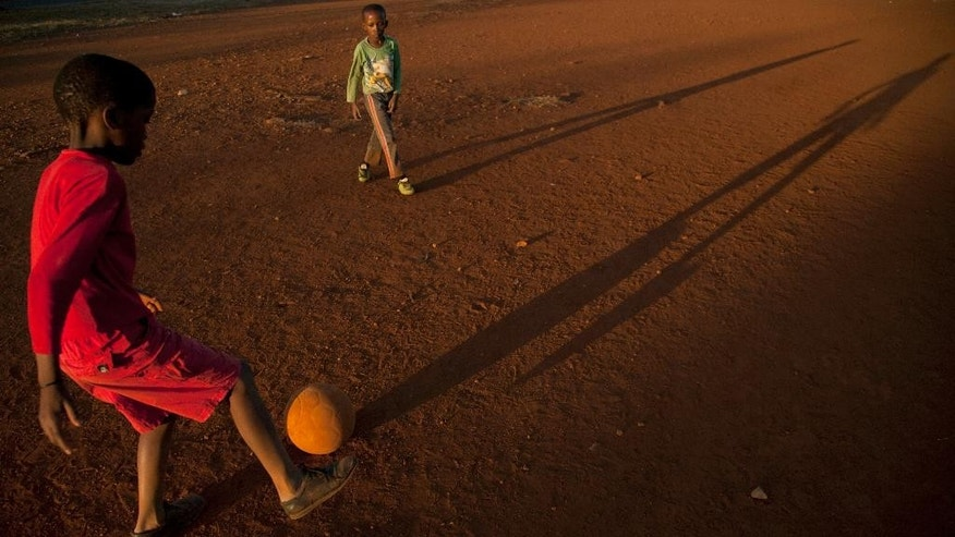 Young boys play soccer on a dusty field in Thokoza township east of Johannesburg, South Africa, Thusday, May 28, 2015. When South Africa won the right to host Africa's first World Cup, it was seen as a heartwarming reward for Nelson Mandela and a country that had shaken off decades of apartheid. Today, the picture seems very different. The image of South Africa's World Cup in 2010 has been shattered by allegations that its bid over a decade ago was involved in bribes of more than $10 million to secure FIFA votes — possibly with the knowledge or involvement of the South African government. (AP Photo/Themba Hadebe)
