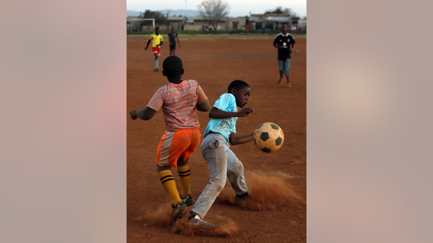 Young boys play soccer on a dusty field in Thokoza township east of Johannesburg, South Africa, Thursday, May 28, 2015.  The image of South Africa's 2010 World Cup has been shattered by allegations that its bid over a decade ago was involved in bribes of more than $10 million to secure FIFA votes _ possibly with the knowledge or involvement of the South African government.  (AP Photo/Themba Hadebe)