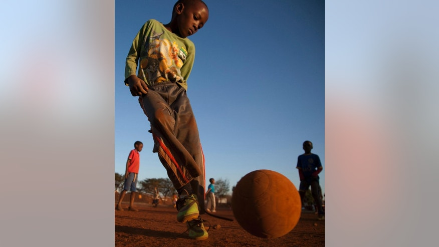 Young boys play soccer on a dusty field in Thokoza township east of Johannesburg, South Africa, Thusday, May 28, 2015. The image of South Africa's 2010 World Cup has been shattered by allegations that its bid over a decade ago was involved in bribes of more than $10 million to secure FIFA votes _ possibly with the knowledge or involvement of the South African government. (AP Photo/Themba Hadebe)