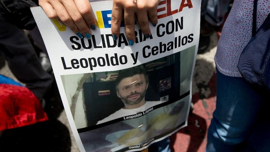 "A supporter of jailed opposition leader Leopoldo Lopez holds a poster of him during an anti-government protest in Caracas, Venezuela, Saturday, May 30, 2015. Lopez and fellow imprisoned former mayor Daniel Ceballos say they launched a hunger strike last weekend to protest what they see as creeping authoritarianism. Government officials have said Lopez is still eating, but the men's families affirm that they have stopped. The poster reads in Spanish: ""Solidarity with Leopoldo and Ceballos."" (AP Photo/Fernando Llano)"