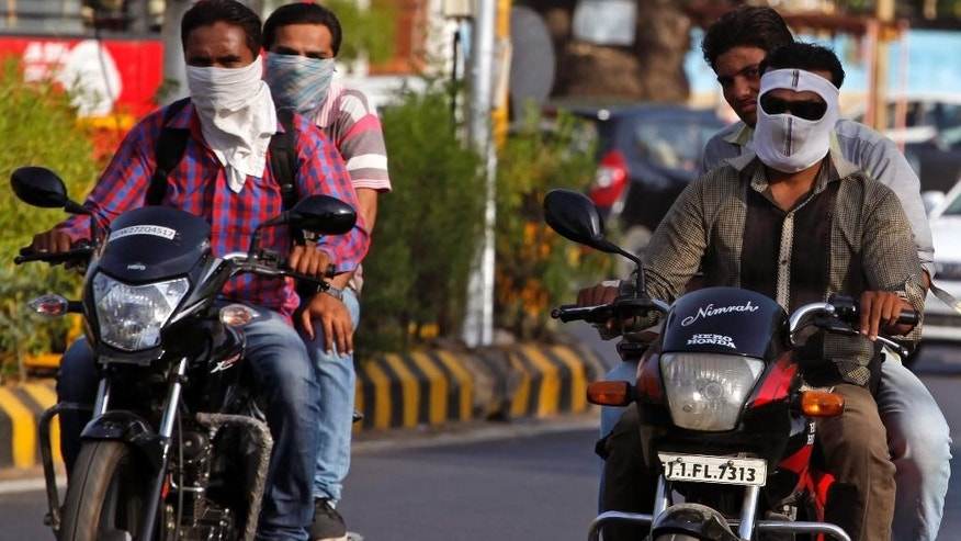 Indian men covers their face with a scarf to protect themselves from the heat on a hot summer day in Ahmadabad, India, Friday, May 29, 2015. Dizzying temperatures caused water shortages in thousands of Indian villages and killed hundreds more people over the past day, driving the death toll from a weeks long heat wave to more than 1,000, officials said Friday. (AP Photo/Ajit Solanki)