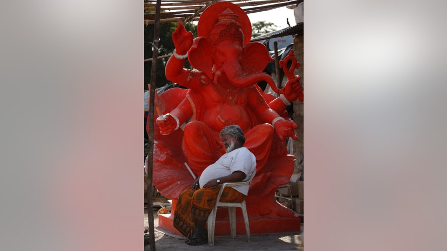 An Indian man catches a nap in between work as he sits in front of an idol of elephant headed Hindu God Ganesha in Ahmadabad, India, Friday, May 29, 2015. Dizzying temperatures caused water shortages in thousands of Indian villages and killed hundreds more people over the past day, driving the death toll from a weeks long heat wave to more than 1,000, officials said Friday. (AP Photo/Ajit Solanki)