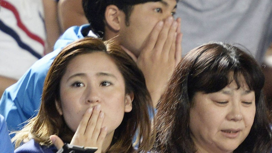 May 30, 2015: Japanese soccer fans react to a strong earthquake as they watch a J-League soccer match between the Shonan Bellmare and the Sanfrecce Hiroshima at BMW Stadium in Hiratsuka.