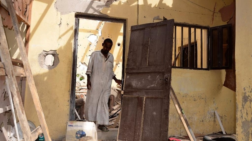 A man inspects a house damaged in Saturday's rocket propelled grenades by Islamic extremist in Maiduguri, Nigeria, Sunday, May 31, 2015. A bomb injured four people in a market Sunday in Maiduguri, a day after the northeastern Nigerian city was hit by a suicide bomber who killed 16 in a mosque. (AP Photo/Jossy Ola)