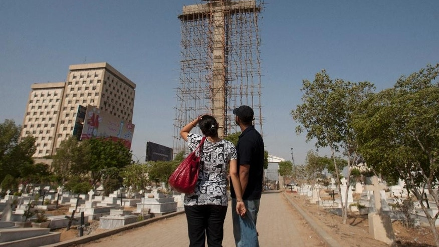 In this photo taken on Monday, May 18, 2015, a Pakistani Christian couple look at large cross, under construction at a cemetery in Karachi, Pakistan. Towering over this violent port city in Pakistan, where Islamic militant attacks and gangland shootings remain common, is an uncommon sight in this Muslim-majority country: a 42-meter (140-foot) Christian cross. The cross, being built by a businessman who said the idea came to him in a dream, is rising as Christians in Pakistan often face discrimination. (AP Photo/Shakil Adil)