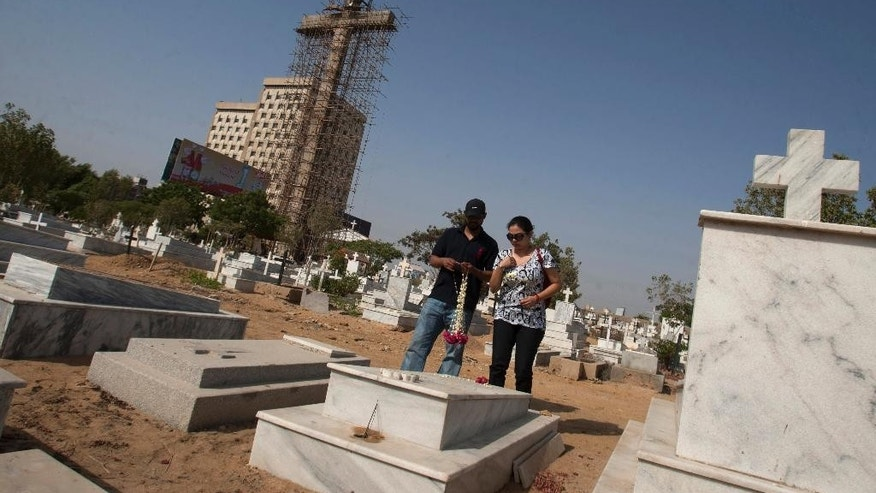 In this photo taken on Monday, May 18, 2015, a Pakistani Christian couple visit a cemetery where a large cross is under construction,  in Karachi, Pakistan. Towering over this violent port city in Pakistan, where Islamic militant attacks and gangland shootings remain common, is an uncommon sight in this Muslim-majority country: a 42-meter (140-foot) Christian cross. The cross, being built by a businessman who said the idea came to him in a dream, is rising as Christians in Pakistan often face discrimination. (AP Photo/Shakil Adil)