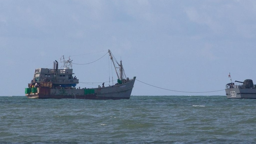 A Myanmar navy boat, right, tows a boat with migrants off Myanmar's Thameehla island, south of Irrawaddy division, Sunday, May 31, 2015. The wooden boat was one of more than half-dozen that have either washed to Southeast Asian shores or been rescued in the last month following a massive, regional crackdown on human trafficking networks. (AP Photo/Gemunu Amarasinghe)
