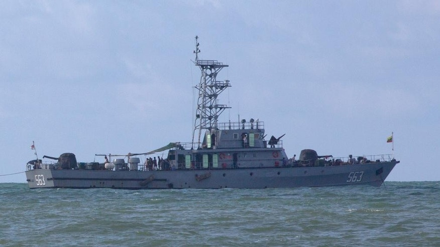 A Myanmar navy boat with migrants onboard seen off Myanmar's Thameehla Island, south of Irrawaddy division, Bay of Bengal, Sunday, May 31, 2015. Myanmar's navy detained journalists on Sunday trying to reach a boat anchored near a remote island where more than 700 migrants were being held after their ship was found drifting off the western coast. (AP Photo/Gemunu Amarasinghe)