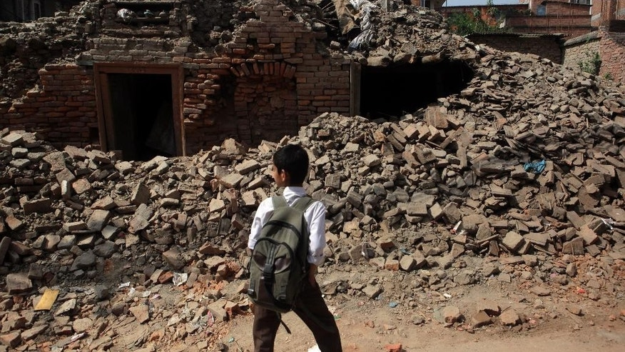 A Nepalese boy walks past a collapsed building close to his school, as thousands of schools across the districts worst hit by two major earthquakes in Nepal reopened Sunday, in Kathmandu, Nepal, Sunday, May 31, 2015. With most school buildings damaged or unsafe, the Education Ministry ordered that classes be held in temporary classrooms. According to a UNICEF statement, 32,000 classrooms were destroyed and 15,352 classrooms were damaged after the two major earthquakes in Nepal. (AP Photo/Niranjan Shrestha)