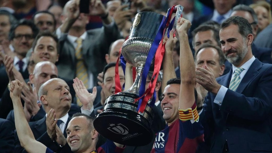 Spain's King Felipe VI, right, applauds as Barcelona's Andres Iniesta, left and Xavi Hernandez lift the cup after winning the final of the Copa del Rey soccer match 3-1against Athletic Bilbao at the Camp Nou stadium in Barcelona, Spain, Saturday, May 30, 2015. (AP Photo/Emilio Morenatti)
