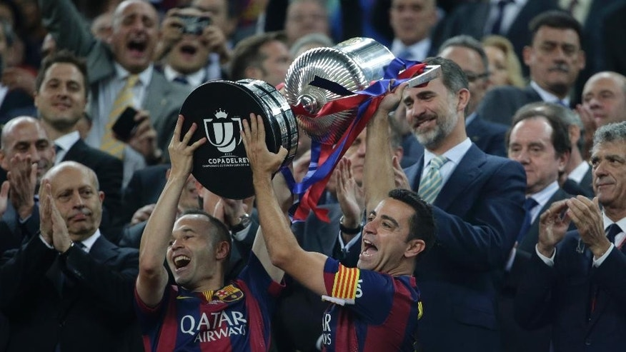 Barcelona's Andres Iniesta, left and Xavi Hernandez lift the cup in front to Spain's King Felipe V1 after winning the final of the Copa del Rey soccer match 3-1against Athletic Bilbao at the Camp Nou stadium in Barcelona, Spain, Saturday, May 30, 2015. (AP Photo/Emilio Morenatti)