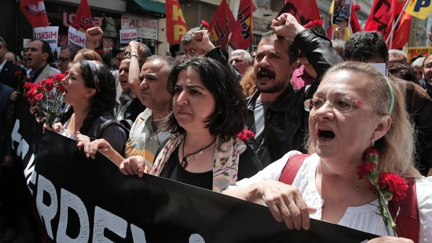 Holding carnations and banners demonstrators chant slogans to mark the second anniversary of the start of 2013 nationwide anti-government protests in Istanbul, Turkey, Sunday, May 30, 2015.  Thousands of protests were sparked two years ago by opposition to government plans to uproot trees at Gezi Park and to build a shopping center.  (AP Photo/Lefteris Pitarakis)
