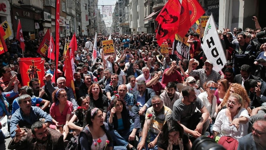 Holding carnations, banners and pictures of the people that lost their lives in the Gezi Park protests, demonstrators chant slogans to mark the second anniversary of the start of 2013 nationwide anti-government protests in Istanbul, Turkey, Sunday, May 30, 2015.  Thousands of protests were sparked two years ago by opposition to government plans to uproot trees at Gezi Park and to build a shopping center.  (AP Photo/Lefteris Pitarakis)