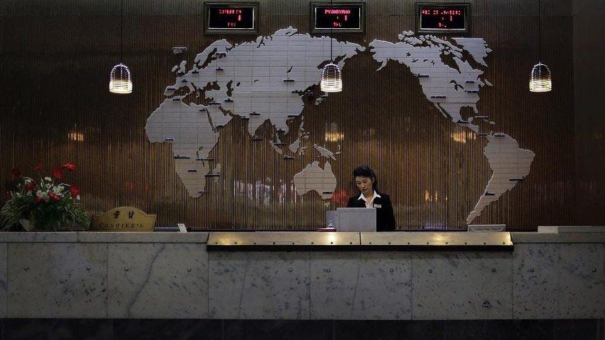 "FILE - In this Thursday, Oct. 23, 2014, file photo, a hotel staff member stands at a reception desk of a hotel, decorated with a map of the world on the wall, in Pyongyang, North Korea. Fresh off a drastic, half-year ban that closed North Korea's doors to virtually all foreigners over fears they would spread the Ebola virus - despite the fact that there were no cases of Ebola reported anywhere in Asia - the country is once again determined to show off its ""socialist fairyland"" to tourists. (AP Photo/Wong Maye-E, File)"