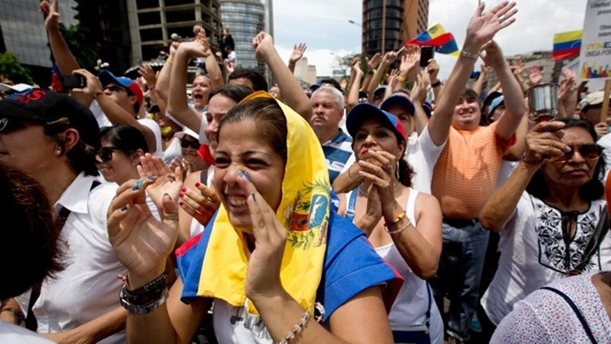Demonstrators cheer Lilian Tintori, the wife of jailed opposition leader Leopoldo Lopez, during an anti-government protest in Caracas, Venezuela, Saturday, May 30, 2015. Lopez and his supporters are calling for a date for legislative elections that the government has promised to hold sometime in November or December, as well as the release of jailed opposition politicians they consider political prisoners. (AP Photo/Fernando Llano)