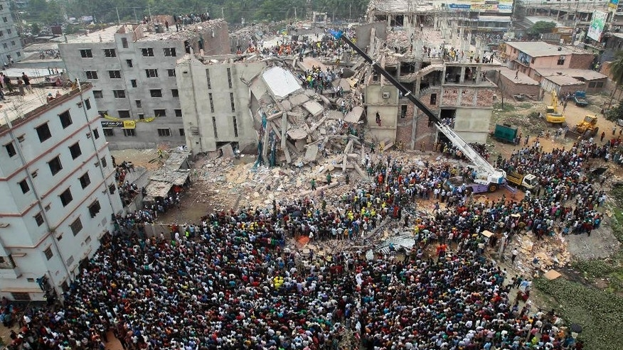 FILE - In this April 25, 2013 file photo, Bangladeshi people gather as rescuers look for survivors and victims at the site of Rana Plaza building that collapsed a day before, in Savar, near Dhaka, Bangladesh. Authorities in Bangladesh said they will file murder charges against 41 people including the building's owner,  Sohel Rana, and his parents and more than a dozen government officials, for their direct role behind the deaths of 1,137 people in the collapse of Rana Plaza. (AP Photo/A.M.Ahad, File)