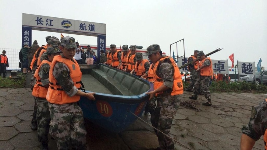 Rescue workers prepare to head out on boats on the Yangtze River to search for missing passengers after a ship capsized in central China's Hubei province Tuesday, June 2, 2015.  The passenger ship carrying more than 450 people sank overnight in the Yangtze River during a storm in southern China, the official Xinhua News Agency reported Tuesday. (Chinatopix Via AP) CHINA OUT