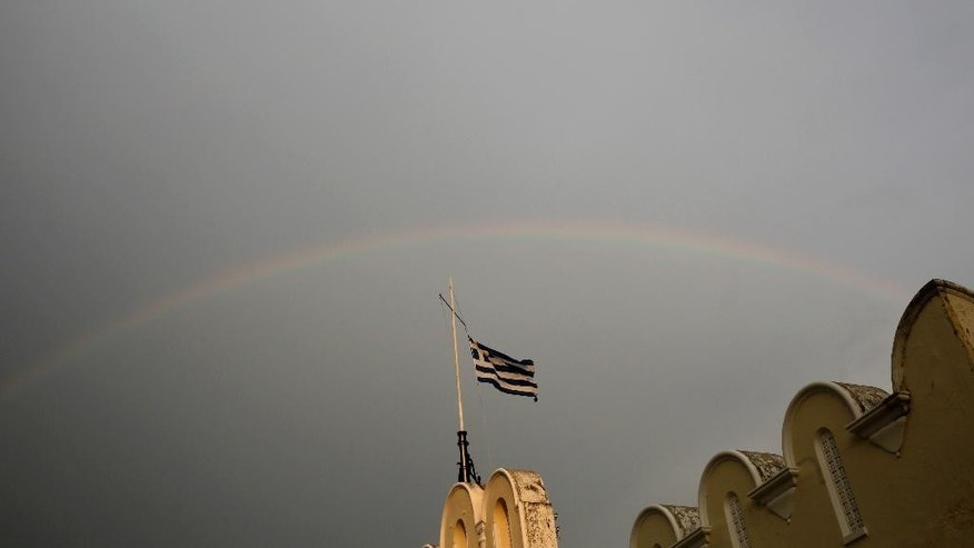 A Greek flag flies on top of the municipality market  with rainbow on the background on Kos island, Greece, Friday, May 29, 2015. Bank deposits in Greece have hit their lowest in more than a decade, according to data released Friday, as Greeks concerned about the painfully slow pace of their government's talks with bailout creditors withdrew savings in an orderly but steady flow.(AP Photo/Petros Giannakouris)