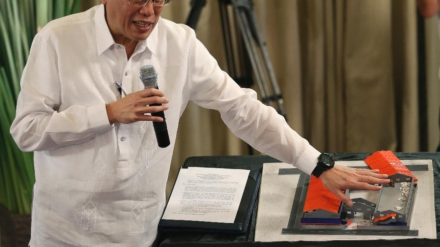 Philippine President Benigno Aquino III points at a scale model of the rubber slipper factory Kentex Manufacturing Corp that left 72 people dead during a fire as he holds a press conference at the Malacanang Presidential Palace in Manila, Philippines Monday, June 1, 2015. Aquino said charges will be filed against all those responsible for last month's factory fire that left 72 people dead, including local officials and fire bureau personnel who ignored the establishment's failure to meet safety requirements.(AP Photo/Aaron Favila)
