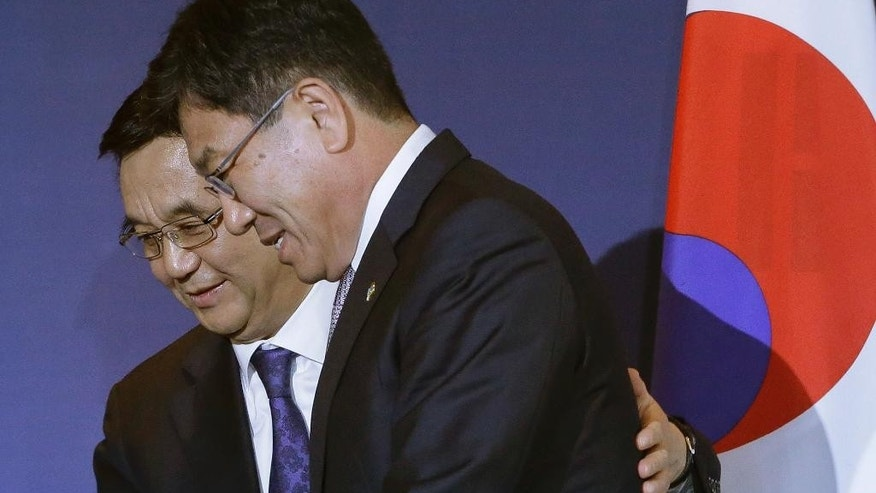 Chinese Commerce Minister Gao Hucheong, left, and his South Korean counterpart Yoon Sang-jick leave after signing documents for FTA or Free Trade Agreement during a signing ceremony in Seoul, South Korea Monday, June 1, 2015. South Korea and China signed a free trade deal that will remove tariffs on more than 90 percent of goods over two decades. (AP Photo/Ahn Young-joon)