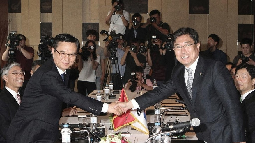 Chinese Commerce Minister Gao Hucheong, left, shakes with his South Korean counterpart Yoon Sang-jick at their meeting before signing documents for FTA or Free Trade Agreement in Seoul, South Korea Monday, June 1, 2015. South Korea and China signed a free trade deal that will remove tariffs on more than 90 percent of goods over two decades. (AP Photo/Ahn Young-joon)
