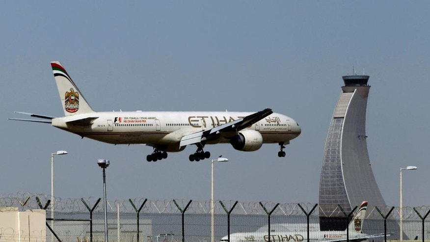 FILE - In this May 4, 2014 file photo, an Etihad Airways plane prepares to land at the Abu Dhabi airport in the United Arab Emirates. The United Arab Emirates' national carrier has formally submitted a document to the United States government rebutting allegations by U.S. carriers that it receives unfair subsidies. (AP Photo/Kamran Jebreili, File)