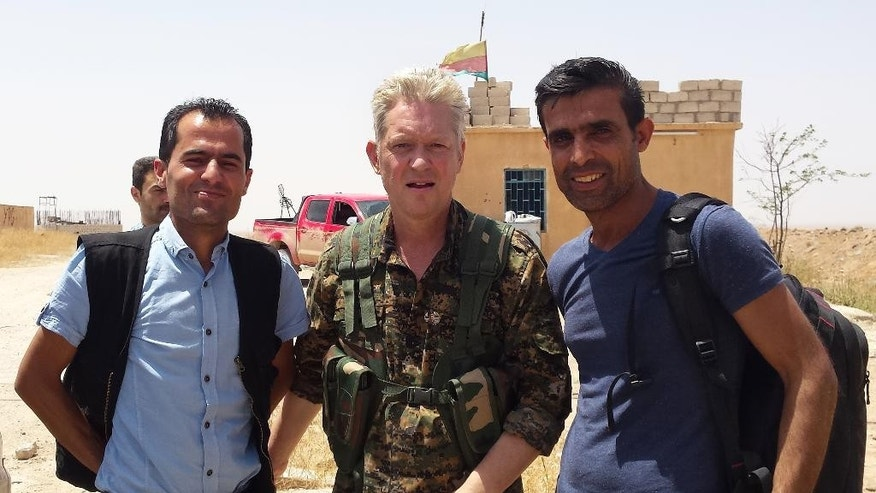 "In this handout photo provided by Kurdish journalist Mohammed Hassan, taken on May 19, 2015, Michael Enright, center, a British actor who has had minor roles in Hollywood films, wears the Kurdish fighters military uniform after he joined them battling against the Islamic State group, near Tel Tamr town, northeast Syria. Enright, who played a deckhand in ""Pirates of the Caribbean: Dead Man's Chest,"" appears in a video released by the Kurdish People's Protection Units, known as the YPG. The video shows him in a trench with other fighters firing an assault rifle. (Mohammed Hassan via AP )"