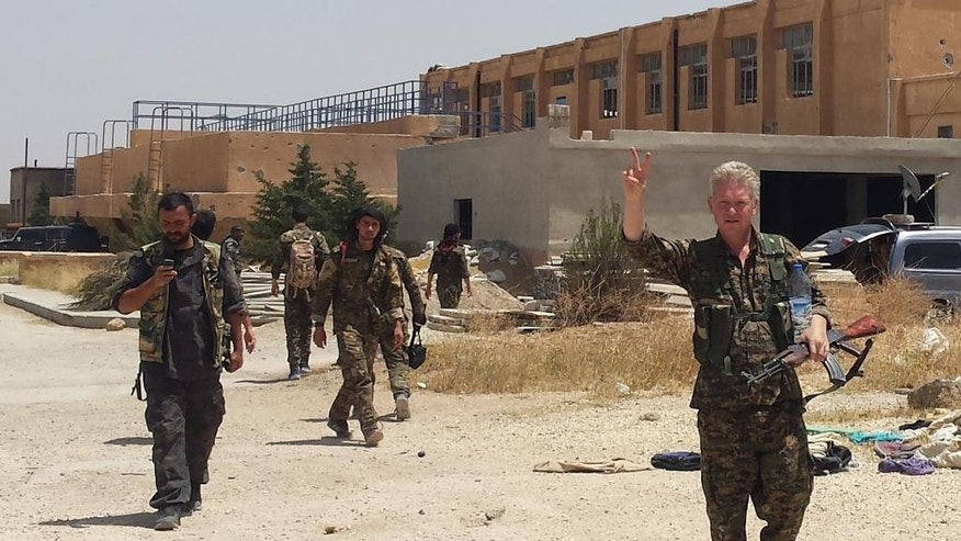 "In this handout photo provided by Kurdish journalist Mohammed Hassan, taken on May 19, 2015, Michael Enright, right foreground, a British actor who has had minor roles in Hollywood films, wears the Kurdish fighters military uniform and flashes the victory sign after he joined them battling against the Islamic State group, near Tel Tamr town, northeast Syria. Enright, who played a deckhand in ""Pirates of the Caribbean: Dead Man's Chest,"" appears in a video released by the Kurdish People's Protection Units, known as the YPG. The video shows him in a trench with other fighters firing an assault rifle. (Mohammed Hassan via AP )"