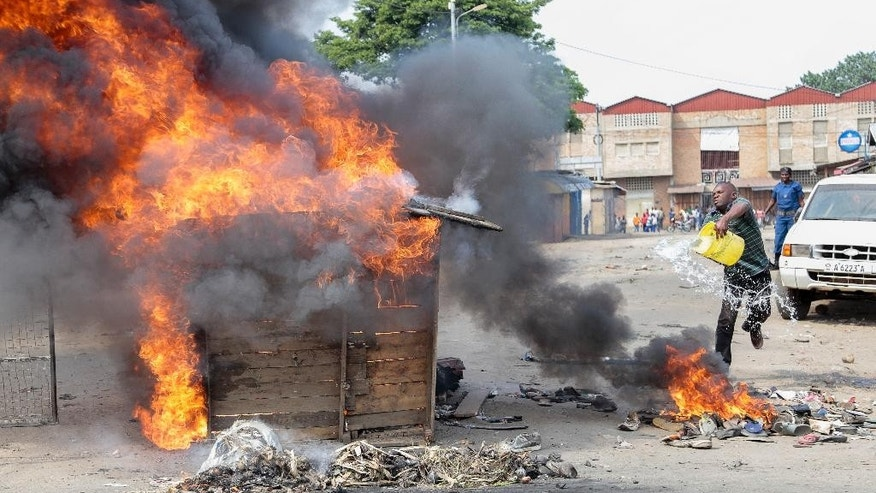 FILE - In this Tuesday, May 26, 2015 file photo, an opposition protester throws water to put out flames on a burning barricade set by him and others, when it started to burn overhead electricity cables providing power to the neighborhood, in the Buyenzi district of the capital Bujumbura, Burundi. Protests continued in the capital Tuesday, with demonstrators saying they will continue until President Pierre Nkurunziza steps down at the end of his second term. (AP Photo/Berthier Mugiraneza, File)