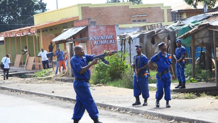 A policeman fires live rounds towards opposition demonstrators to prevent them from reaching a main road, in the Mutakura neighborhood of the capital Bujumbura, Burundi Tuesday, June 2, 2015. Burundi's electoral commission is considering alternative dates for national elections amid growing calls for the polls to be postponed due to political unrest, an official said Tuesday as anti-government protests returned to parts of the capital. (AP Photo/Berthier Mugiraneza)