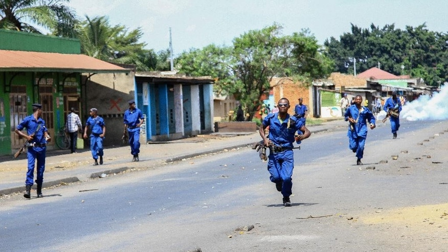 Policemen run down the road during confrontations with opposition demonstrators, in the Mutakura neighbourhood of the capital Bujumbura, Burundi Tuesday, June 2, 2015. Burundi's electoral commission is considering alternative dates for national elections amid growing calls for the polls to be postponed due to political unrest, an official said Tuesday as anti-government protests returned to parts of the capital. (AP Photo/Berthier Mugiraneza)