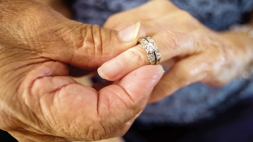 Robert Kirker puts a wedding ring, lost for 30 years, on his wife Ofelia's hand at their home in Las Cruces, N.M., May 27, 2015. (Jett Lowe/Las Cruces Sun-News via AP)