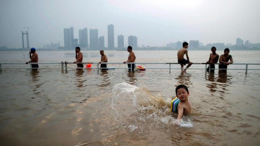 FILE - In this file photo taken July 15, 2012, residents take advantage of the high water level to cool off in a flooded park on the banks of the Yangtze River in Wuhan in central China's Hubei province. The Yangtze, one of the longest and most famous rivers in the world, sometimes floods during the summer monsoon season and parts of it are heavily polluted from industry and agriculture.(Chinatopix Via AP, File) CHINA OUT
