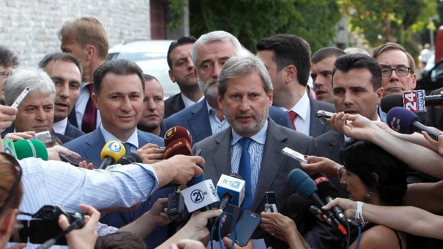 EU commissioner for Neighborhood Policy & Enlargement Negotiations Johannes Hahn, center, talks for the media in presence of the leader of Macedonian opposition Social Democrats Zoran Zaev, second from right, Macedonian Prime Minister and leader of the VMRO-DPMNE conservative party Nikola Gruevski, second from left, the leader of the Democratic Union for Integrations Ali Ahmeti, left and the leader of the Democratic Party of the Albanians Menduh Thaci, center rear, after their meeting at the EU Ambassador's residence in Skopje, Macedonia, on Tuesday, June 2, 2015. Macedonia should hold early elections by the end of April next year, EU commissioner Hahn said after the talks with Macedonia's four top political leaders in Skopje on Tuesday. (AP Photo/Boris Grdanoski)