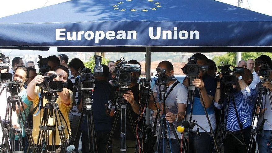 Media representatives, under an EU branded umbrella, attend a news conference of the EU commissioner for Neighborhood Policy & Enlargement Negotiations Johannes Hahn following his meeting with the leaders of the four most relevant parties in Macedonia at the EU Ambassador's residence in Skopje, Macedonia, on Tuesday, June 2, 2015. Macedonia should hold early elections by the end of April next year, EU commissioner Hahn said after the talks with Macedonia's four top political leaders in Skopje on Tuesday. (AP Photo/Boris Grdanoski)