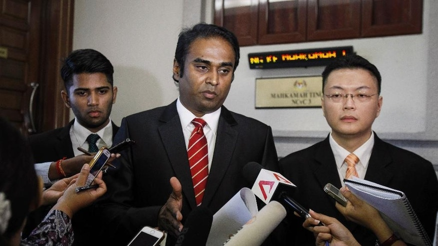 "Lawyers Arunan Selvaraj, center, and Gary Chuah, right, speak to the media at the high court in Kuala Lumpur, Malaysia on Tuesday, June 2, 2015. Two Malaysian boys whose father was a passenger on the missing Malaysia Airlines Flight 370 that vanished in March last year secured an out of court settlement in the tragedy's first legal case against Malaysia Airlines and the government. Selvaraj said the mother of the boys decided to accept compensation on their behalf so that they can ""move forward with their life."" (AP Photo/Joshua Paul)"