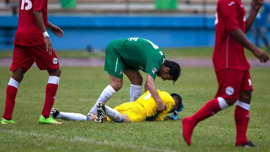 New York Cosmos' Raul Gonzalez helps Cuba's goalkeeper Sandy Sanchez after a tackle during their friendly soccer match at the Pedro Marrero stadium in Havana, Cuba, Tuesday, June 2, 2015. New York Cosmos won the game 4-1. (AP Photo/Ramon Espinosa)