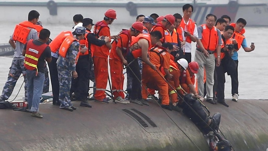 Rescuers help lift a survivor pulled from the capsized cruise ship on the Yangtze River in Jianli in central China's Hubei province Tuesday June 2, 2015. Divers on Tuesday pulled survivors from inside the overturned cruise ship, state media said, giving some small hope to an apparently massive tragedy with well over 400 people still missing on the river. (Chinatopix Via AP) CHINA OUT