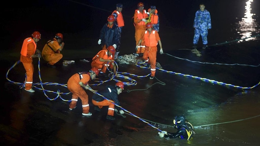 In this Tuesday, June 2, 2015 photo released by China's Xinhua News Agency, rescuers work at the site of the overturned passenger ship in the Jianli section of the Yangtze River in central China's Hubei Province. Hopes dimmed Wednesday for rescuing more than 400 people still trapped aboard the capsized river cruise ship that overturned in stormy weather about 36 hours earlier, as hundreds of rescuers searched the Yangtze River site in what could become the deadliest Chinese maritime accident in decades. (Xiao Yijiu/Xinhua via AP) NO SALES