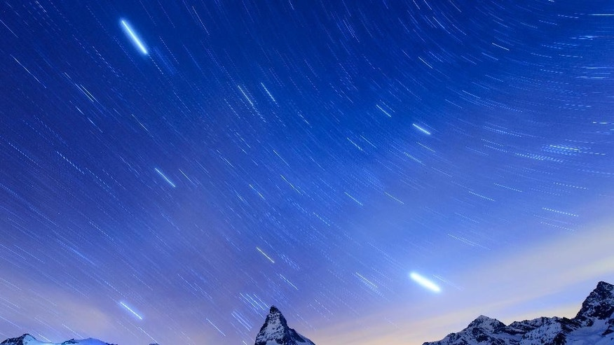 FILE - In this , April 13, 2015 file photo, taken  with a long time exposure, stars are pictured over the Matterhorn mountain, near  Zermatt, Switzerland. Switzerland's most famous mountain, will be closed to climbers on the 150th anniversary next month of the first ascent.The Alpine resort of Zermatt says the 24-hour shutdown July 14 is intended as a mark of respect to more than 500 climbers who have died on the mountain, starting with four of the seven-strong team that first reached the summit in 1865.  (Jean-Christophe Bott/Keystone via AP,File)