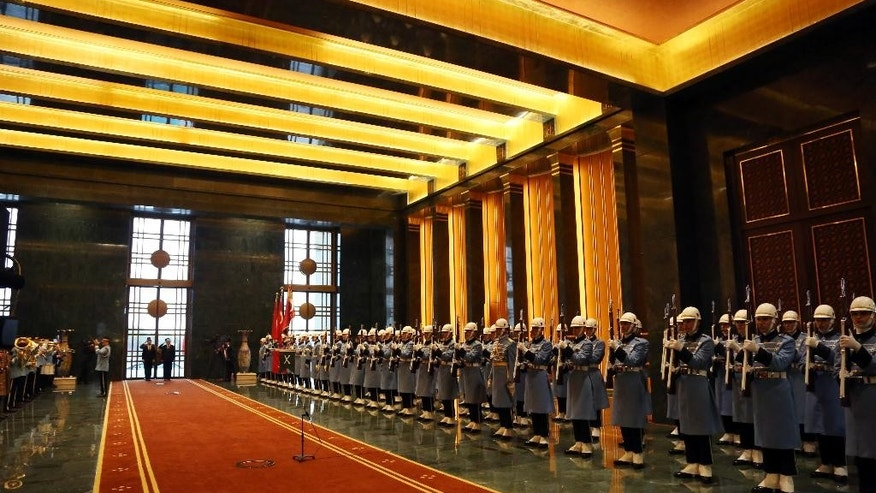 FILE - In this March 12, 2015 file photo, honour guard wait for a ceremony inside the new palace of Turkey's President Recep Tayyip Erdogan. Erdogan has invited Kemal Kilicdaroglu, the main opposition Republican People's Party, or CHP, leader, to inspect toilets in his lavish, 1,150-room palace after the politician claimed that it had gold-plated toilet seats. CHP leader and other opposition parties accuse Erdogan of excessive spending by the president of tax-payer money on luxuries. On Sunday, Erdogan told state-run TRT television in an interview that he would resign if Kilicdaroglu found a gold-plated toilet seat at the $620 million palace. Turkey holds a general election on Sunday.(AP Photo/Burhan Ozbilici, File)