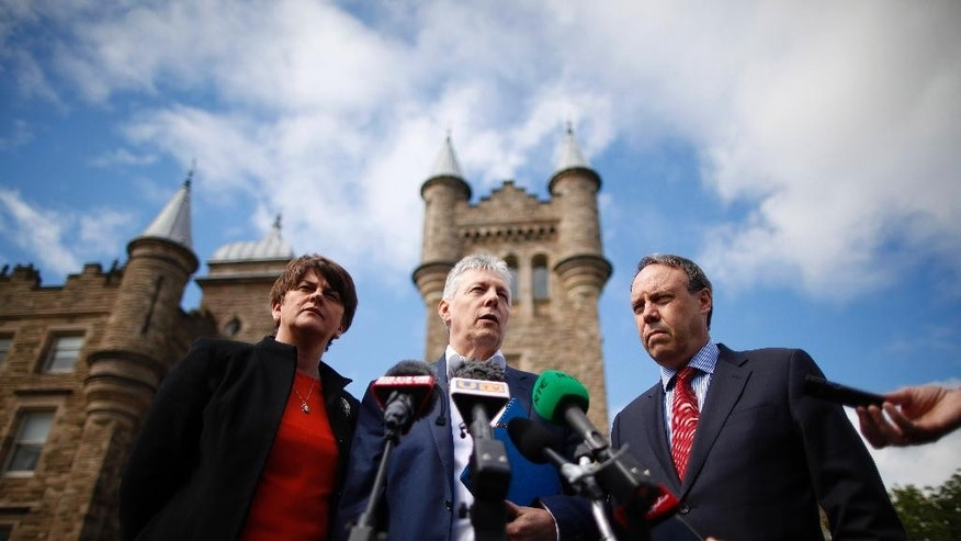 Northern Ireland First Minister Peter Robinson and leader of the Democratic Unionist Party, center, and party members Arlene Foster and Nigel Dodds MP, speak to the media at Stormont, Northern Ireland, Tuesday June 2, 2015. The British and Irish governments convened Northern Ireland's quarreling parties in a bid to save their Catholic-Protestant coalition.  (AP Photo/Peter Morrison)