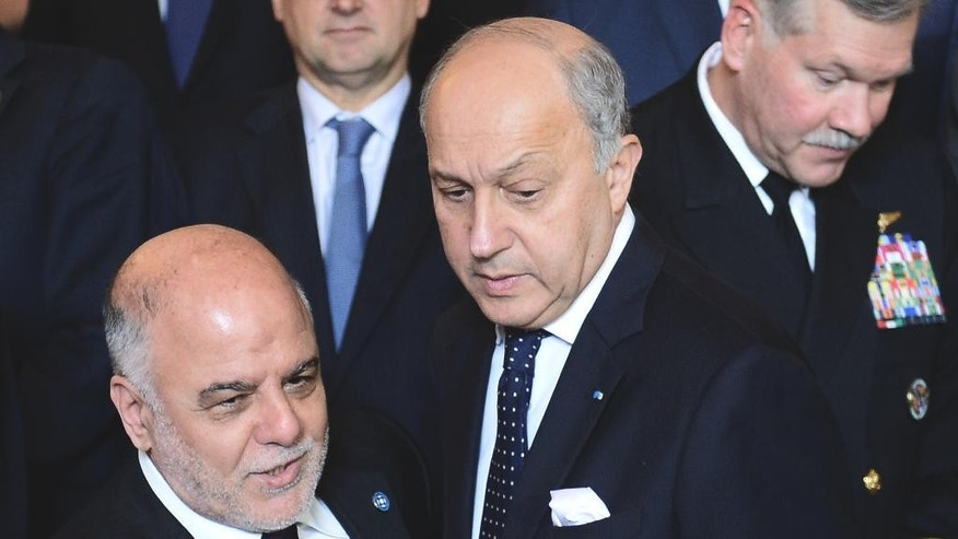 Iraqi Prime Minister Haider al-Abadi, left, and French Foreign Affairs Minister Laurent Fabius arrive to pose for a group photo with Foreign Affairs ministers and members of the anti-Islamic State coalition after a meeting in Paris, France, to discuss strategy in fighting the jihadist militant group, who have made key battlefield advances in recent weeks in Iraq and Syria, Tuesday, June 2, 2015. Iraq's prime minister and international allies are gathering in Paris to re-examine their strategy against Islamic State extremists, after the group's recent gains. The coalition, which includes the United States and France but not Russia, Iran or Syria, is meeting Tuesday after extremists conquered both the Iraqi city of Ramadi and the historic Syrian city of Palmyra. (Stephane de Sakutin/Pool Photo via AP)