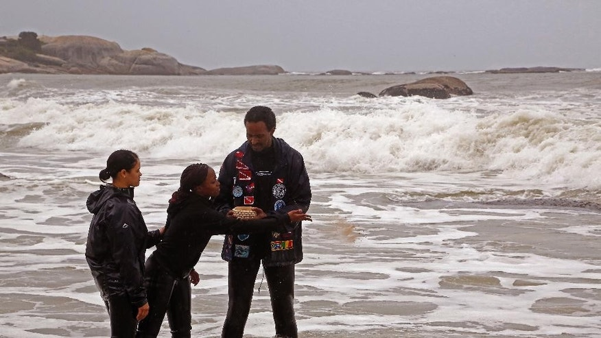 Divers scatter  sand from Mozambique in honor of the doomed slaves from the Sao Jose slave ship at Clifton beach  on the outskirts of  the city of Cape Town, South Africa,  Tuesday, June 2, 2015.  Amid rain and wind, South African and American researchers held a memorial service for slaves who died when the Portuguese ship that was carrying them into bondage sank while sailing to Brazil in 1794. (AP Photo/Schalk van Zuydam)
