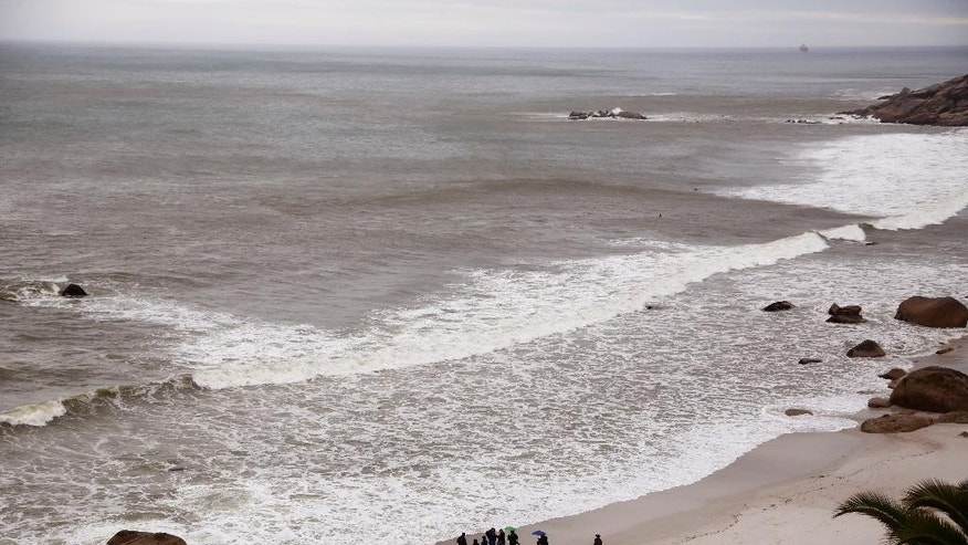 Divers, bottom left, before they enter the ocean to scatter sand from Mozambique in honor of the doomed slaves from the Sao Jose slave ship at Clifton beach  on the outskirts of  the city of Cape Town, South Africa,  Tuesday, June 2, 2015. Amid rain and wind, South African and American researchers held a memorial service for slaves who died when the Portuguese ship that was carrying them into bondage sank while sailing to Brazil in 1794.  (AP Photo/Schalk van Zuydam)