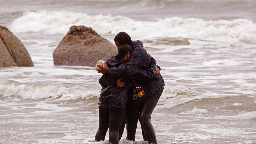 Divers hug each other  after they scattered sand from Mozambique in honor of the doomed slaves from the Sao Jose slave ship at Clifton beach  on the outskirts of  the city of Cape Town, South Africa,  Tuesday, June 2, 2015.  Amid rain and wind, South African and American researchers held a memorial service for slaves who died when the Portuguese ship that was carrying them into bondage sank while sailing to Brazil in 1794. (AP Photo/Schalk van Zuydam)