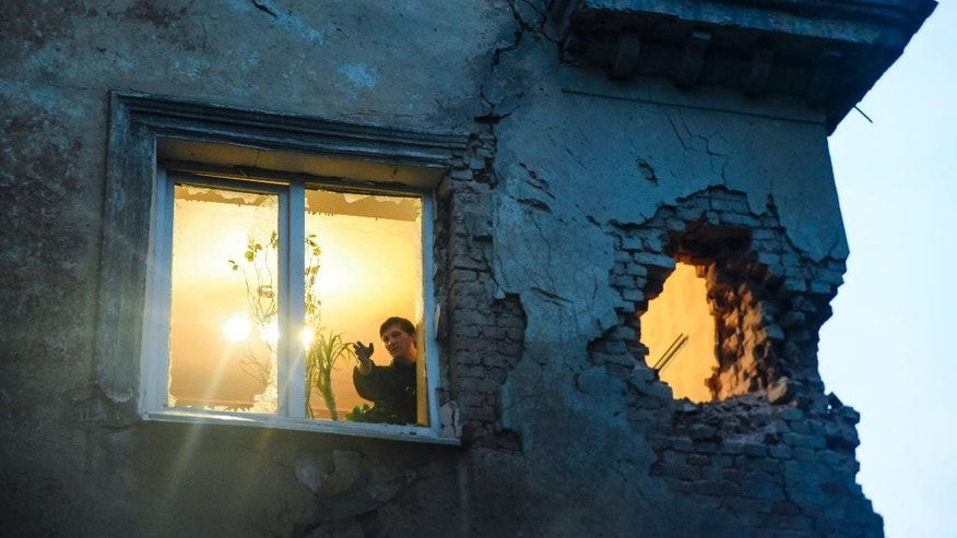 People observe damage in their flat after shelling between Russia-backed separatists and Ukrainian government troops in Donetsk, Eastern Ukraine Monday, June 1, 2015. In a new report released Monday, the U.N. human rights office said that the number of people killed in more than a year of fighting in the east has risen to more than 6,400 people. (AP Photo/Mstyslav Chernov)