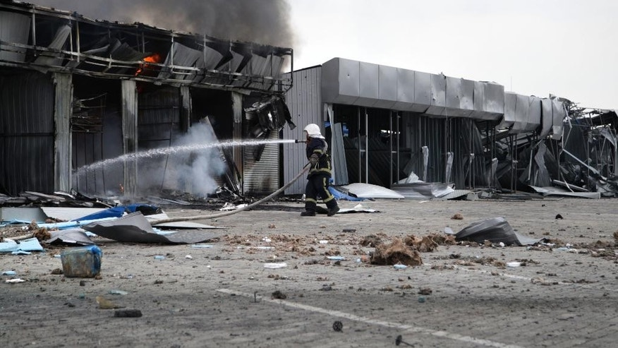 A firefighter works to extinguish the fire at a market destroyed after shelling in Donetsk, Ukraine, Wednesday, June 3, 2015, during battles on Wednesday in eastern Ukraine Territories. Intensified battles around the rebel stronghold of Donetsk on Wednesday left more than a dozen people dead and threatens to tip the country back into full-blown war, according to Ukraine's General Staff.(AP Photo/Alexander Ermochenko)