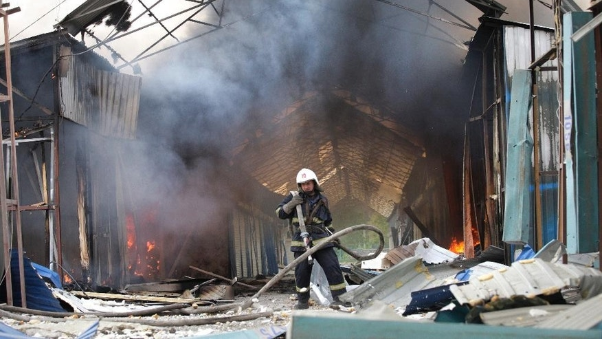 A firefighter extinguishes the fire at a market destroyed after shelling in Donetsk, Ukraine, Wednesday, June 3, 2015, during battles on Wednesday in eastern Ukraine Territories.  Intensified battles around the rebel stronghold of Donetsk on Wednesday left more than a dozen people dead and threatens to tip the country back into full-blown war, according to Ukraine's General Staff. (AP Photo/Alexander Ermochenko)